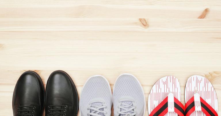 Vista desde arriba de unos zapatos de cuero negros, unas zapatillas y unas chanclas en un suelo de madera