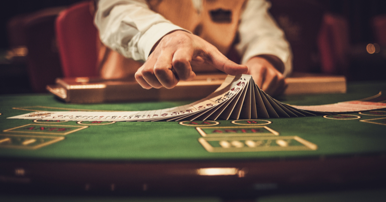 Un crupier manipulando cartas en una mesa de juego de un casino