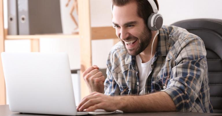 Un joven celebra una victoria mientras juega al casino online desde su ordenador portátil.