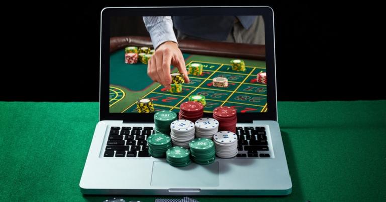 Un ordenador portátil con un crupier colocando fichas en vivo en la pantalla y fichas de casino en el teclado.