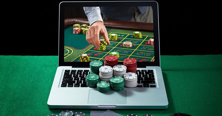 Una partida de póquer que aparece en la pantalla de un portátil con fichas de casino en el teclado.
