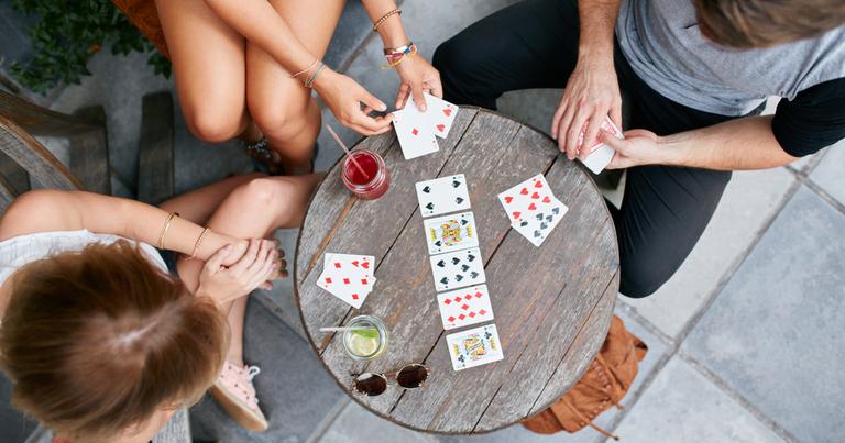 Tres jóvenes adultos juegan a las cartas en una mesa de madera al aire libre.