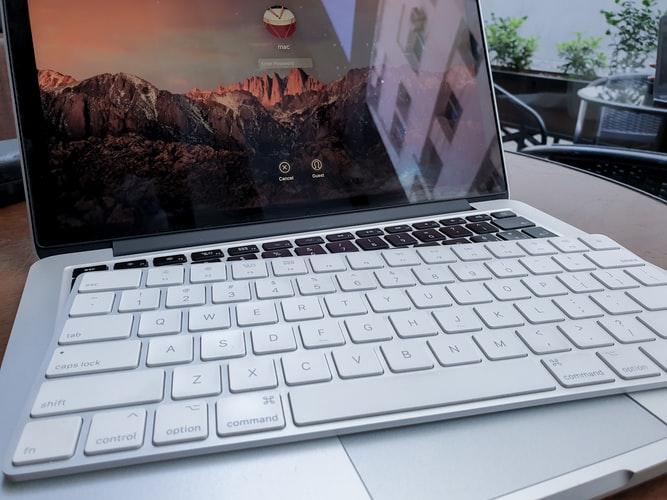 Imagen con un ordenador portátil y un teclado sobre el mismo.